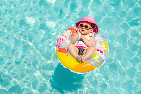 Cute Baby Girl In Sunglasses Floating On Tropical Blue Water Imagens