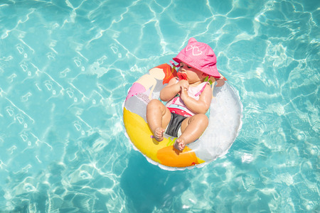 Cute Baby Girl Sleeping On Float In Carribean Blue Water On Beautiful Sunny Day
