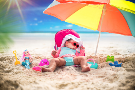 Cute Baby Girl On A Tropical Beach Vacation With Toys