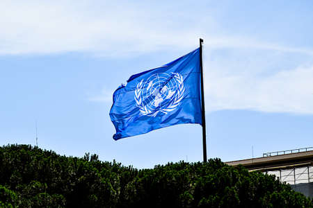 Blue flag of the United Nations waving in a sky with few clouds.