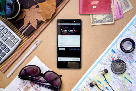 american airlines: KUALA LUMPUR, MALAYSIA - JUNE 14TH, 2016: Modern lifestyle with smartphone to stay connected & browsing using favourite Apps. Book & Check-in flight with AMERICAN AIRLINES Apps.