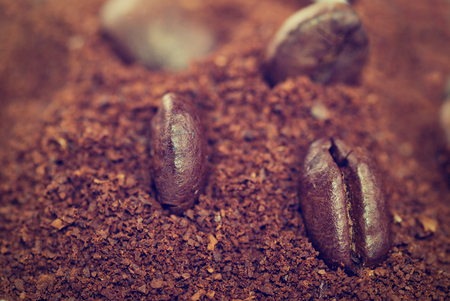 grounded: Coffe beans in the heat of the grounded coffe, macro close-up with retro vintage filter.