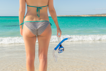 Young woman with snorkel set in front of the ocean Stock Photo