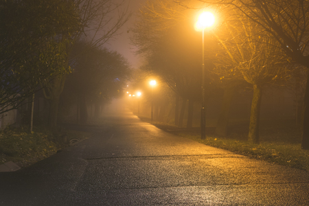 Dark alley in heavy fog iluminated by street lamps Stock Photo