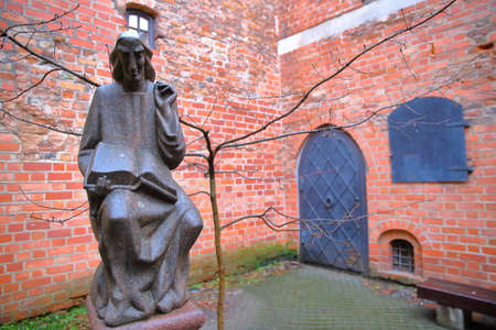 ghetto: VILNIUS, LITHUANIA - JANUARY 2, 2017: A courtyard in the former small Jewish Ghetto with a statue of Metrastininkas (sculptor Vaclovas Krutinis)