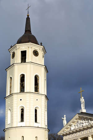pediment: VILNIUS, LITHUANIA - JANUARY 3, 2017: The Belfry (Cathedral Clock Tower) and the  Cathedral on Cathedral Square with a stormy sky