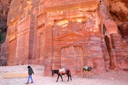 nabatean: PETRA, JORDAN - MARCH 7, 2016: Colorful tombs in the Outer Siq with a local Bedouin leading his donkeys
