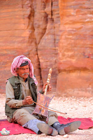 nabatean: PETRA, JORDAN - MARCH 11, 2016: A Bedouin musician playing and singing in the Outer Siq Editorial