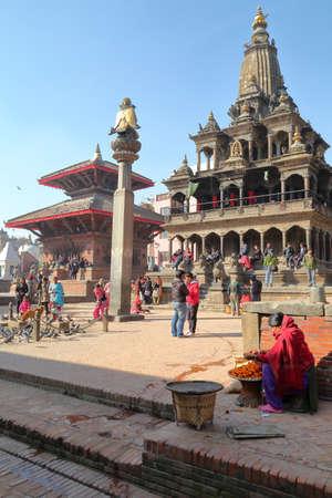 garuda: PATAN, NEPAL - DECEMBER 19, 2014: Garuda statue on column and Krishna Mandir temple at Durbar Square