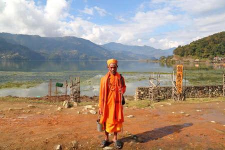 phewa: POKHARA, NEPAL - JANUARY 4, 2015: A Sadhu (Holy man) posing along the shore of Phewa Lake