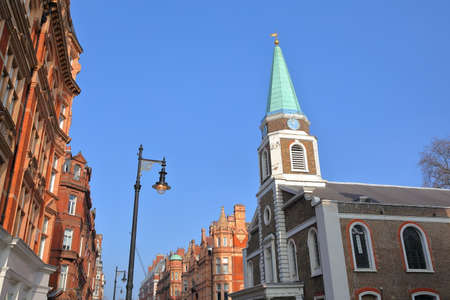 LONDON, UK: Grosvenor Chapel and red brick Victorian houses facades in S Audley Street (borough of Westminster) Stock Photo
