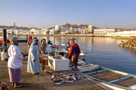 muttrah: MUSCAT, OMAN - FEBRUARY 11, 2012: Fishermen at The Muttrah Fish docks early morning with Muttrah corniche in the Background