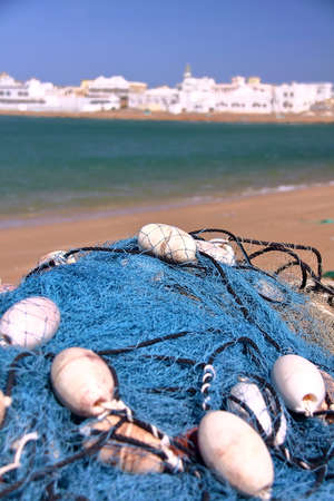 sur: SUR, OMAN: A fishing net with the port of Ayjah in the background