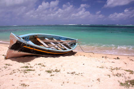 RODRIGUES ISLAND, MAURITIUS: A fishing boat on the beach and the colorful Indian Ocean Zdjęcie Seryjne