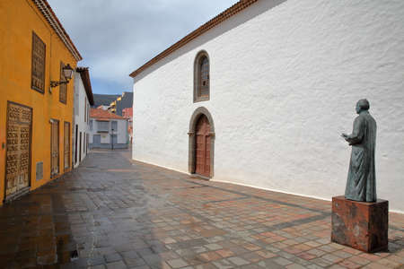 padilla: SAN SEBASTIAN DE LA GOMERA, LA GOMERA, SPAIN - MARCH 18, 2017: The statue of Father Jose Torres Padilla with a colorful facade on the left side and the Church of the Assumption on the right side