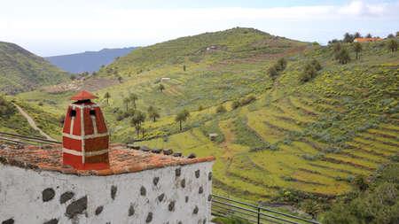 CHIPUDE, LA GOMERA, SPANJE: Groen landschap en terrasvormige velden van Chipude met een traditioneel huis op de voorgrond Stockfoto