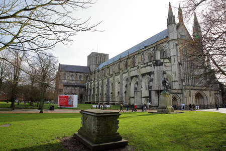 winchester: WINCHESTER, UK - FEBRUARY 4, 2017: Exterior view of the Cathedral with a tomb in the foreground