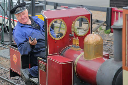 HASTINGS, UK - JULY 23, 2017: Close-up on the driver of a steam train at the Hastings Miniature Railway located at Rock-a-Nore Road