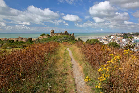 View of Hastings Castle from a path located on the West Hill with the Pier and the sea in the background, Hastings, UK