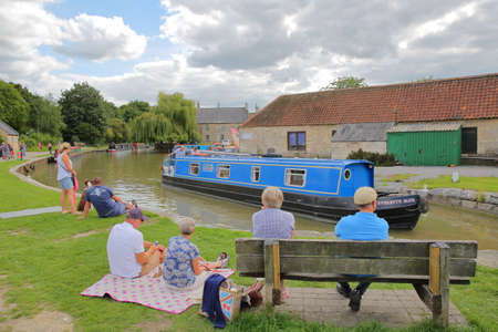 Bradford on Avon, UK - AUGUST 13, 2017: People enjoying a summer day at Canal Wharf with colorful barges on Kennet and Avon Canal Editorial
