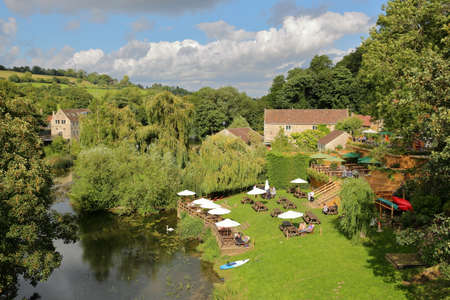 Bradford on Avon, UK - AUGUST 12, 2017: People relaxing in a Pub Garden beside the river Avon in Avoncliff (picture taken from Avoncliff Aqueduct)