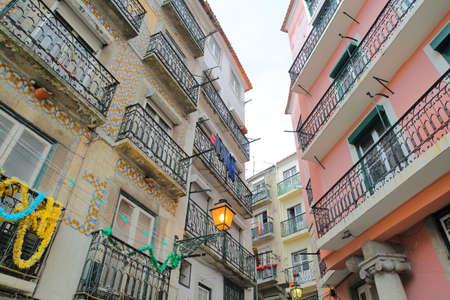 LISSABON, PORTUGAL - 2. NOVEMBER 2017: Hausfassaden verziert mit bunten Fliesen und mit Schmiedeeisengeländerbalkonen in Alfama-Nachbarschaft Standard-Bild - 90642144