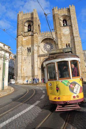 LISBON, PORTUGAL - NOVEMBER 2, 2017: The Cathedral (Se) and a yellow Tram in Alfama neighborhood