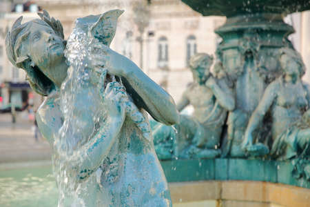 Fountains in Rossio Square, close-up on one of the mermaid statues in Baixa neighborhood, Lisbon, Portugal
