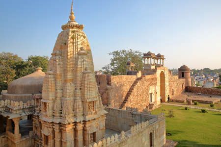 CHITTORGARH, RAJASTHAN, INDIA - DECEMBER 12, 2017: Ratan Singh Palace, located inside the fort (Garh) of Chittorgarh, with a Hindu Temple in the foreground
