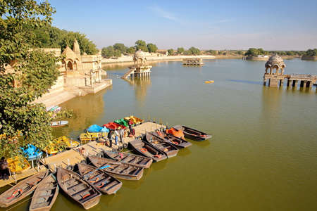 JAISALMER, RAJASTHAN, INDIA - DECEMBER 19, 2017: General view of Gadi Sagar lake with paddling boats in the foreground and chhatris Stock fotó - 96257896