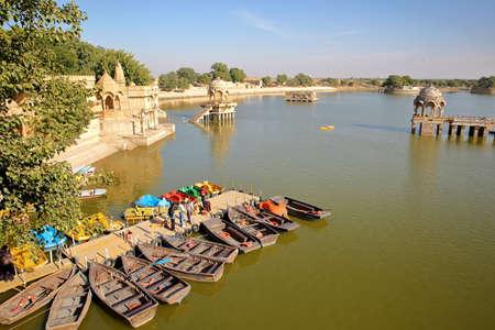 JAISALMER, RAJASTHAN, INDIA - DECEMBER 19, 2017: General view of Gadi Sagar lake with paddling boats in the foreground and chhatris