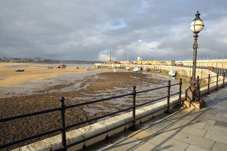 Margate Harbor Arm with mooring boats, the lighthouse and the beach at low tide, Margate, Kent, UK 版權商用圖片