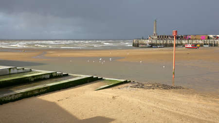 The beach at low tide by stormy and windy weather with Margate Harbor Arm in the background, Margate, Kent, UK