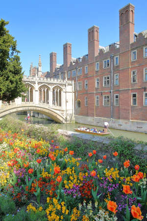 CAMBRIDGE, UK - MAY 6, 2018: The Bridge of Sighs at St John's College University with tourists and students punting on the river Cam with colorful flowers in the foreground
