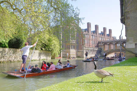 CAMBRIDGE, UK - MAY 6, 2018: The Bridge of Sighs at St Johns College University with tourists and students punting on the river Cam in the foreground