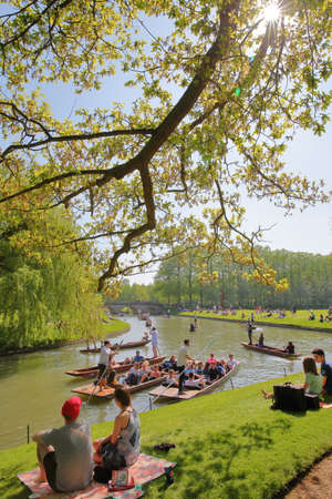 CAMBRIDGE, UK - MAY 6, 2018: Students enjoying a sunny day on the banks of the river Cam at St Johns College University with tourists and students punting
