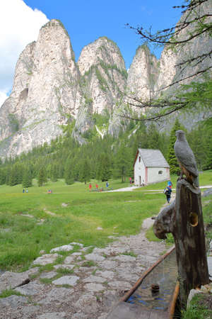 A wooden fountain with carvings along Vallunga Valley above Selva with  Saint Silvestro Chapel and Mount Stevia in the background, Val Gardena, Dolomites, Italy Archivio Fotografico