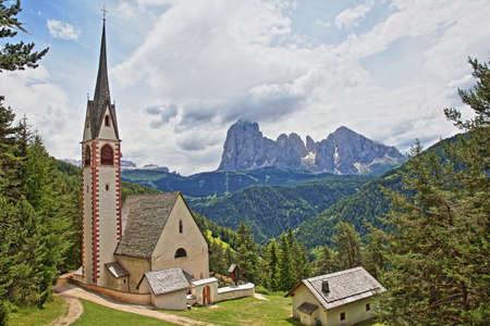 Saint Giacomo church near Santa Cristina and Ortisei with Sassolungo and Sassopiatto mountains in the background, Val Gardena, Dolomites, Italy Stock Photo