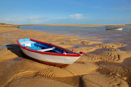 Colorful boats mooring at sunset on the beach of Cacela Velha, a small village located near Tavira, Algarve, Portugal