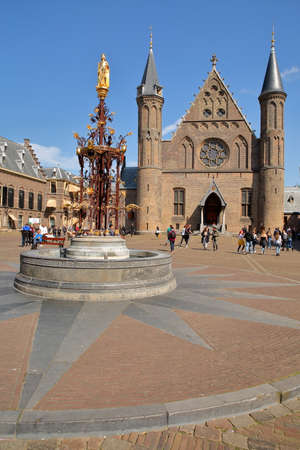 THE HAGUE, NETHERLANDS - APRIL 18, 2019: The Ridderzaal (Knights Hall), which forms the center of the Binnenhof (13 century gothic castle), with the neo-gothic fountain (1883) and the golden statue of King Willem 2 in the foreground Sajtókép