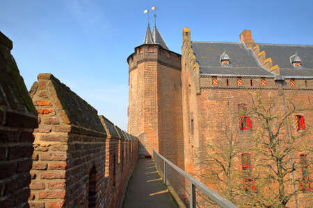 MUIDEN, NETHERLANDS - APRIL 7, 2019: Muiderslot Castle, a medieval castle, with the battlements in the foreground