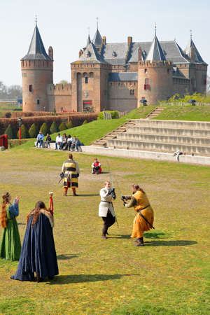MUIDEN, NETHERLANDS - APRIL 7, 2019: Muiderslot Castle, a medieval castle, with characters in medieval costumes in the foreground