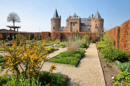 MUIDEN, NETHERLANDS - APRIL 7, 2019: Muiderslot Castle, a medieval castle, with the gardens and spring colors
