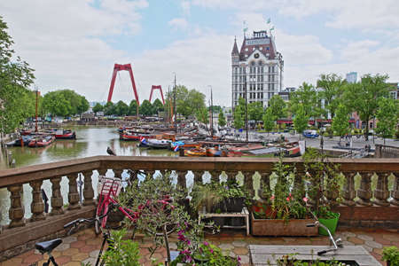 ROTTERDAM, NETHERLANDS - MAY 31, 2019: Oudehaven Harbor with historical houseboats viewed from a balcony, with the White House (Witte Huis) and Willemsbrug Bridge in the background