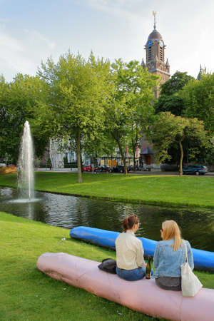 ROTTERDAM, NETHERLANDS - MAY 31, 2019: Two young women relaxing along Westersingel canal on Mauritsweg street, with the Clock Tower of Oud Katholieke Paradijskerk church in the background