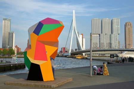 ROTTERDAM, NETHERLANDS - MAY 31, 2019: Erasmus bridge viewed from Willemsplein Square, with colorful scenery in the foreground and modern skyscrapers in the background