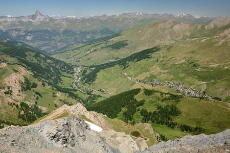 Panoramic view from a mountain ridge overlooking the two valleys of Saint Veran and Ceillac (Cristillan), with Saint Veran village on the right side and Rochebrune Peak in the background, Queyras Regional Natural Park, Southern Alps, France Stock fotó