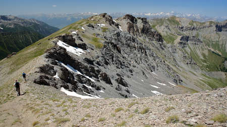 Hiking along a mountain ridge overlooking the two valleys of Saint Veran and Ceillac (Cristillan), with a montain range covered with snow (with Mount Pelvoux) in the background, Queyras Regional Natural Park, Southern Alps, France