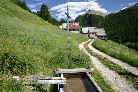 The hamlet Les Chalmettes, located above Ceillac village along Cristillan valley, with pine tree forests in the background and a traditional wooden fountain in the foreground, Queyras Regional Natural Park, Southern Alps, France