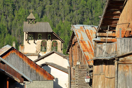 Traditional wooden houses with the bell tower of Saint Sebastien Church in the background, Ceillac, Queyras Natural Park, Southern Alps, France Stock fotó